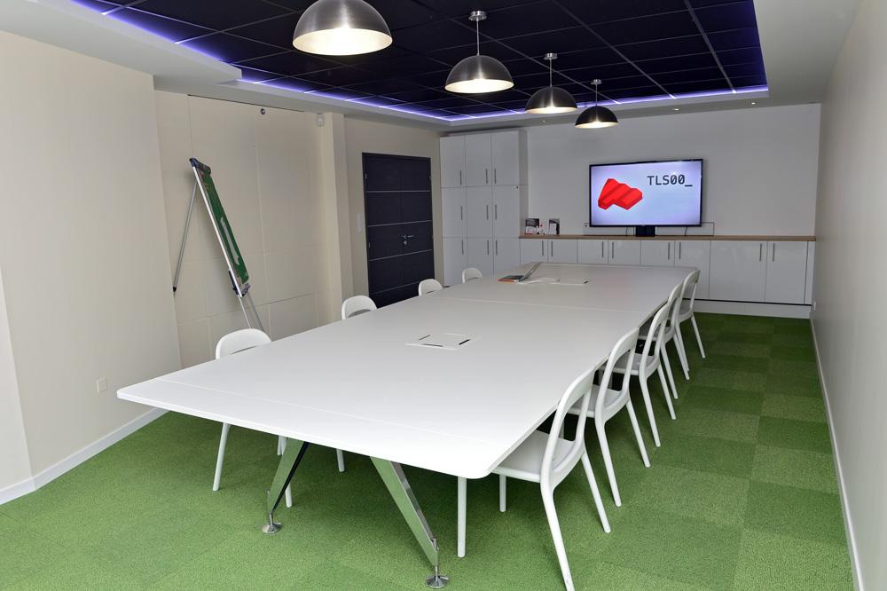 salle de réunion de tls00 avec grande table rectangle blanche et télévision
