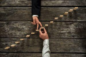 doigts qui montent une échelle en morceaux de bois pour symboliser la croissance
