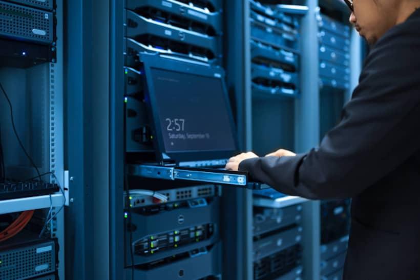 homme qui tape sur un ordinateur portable devant des baies d'un datacenter